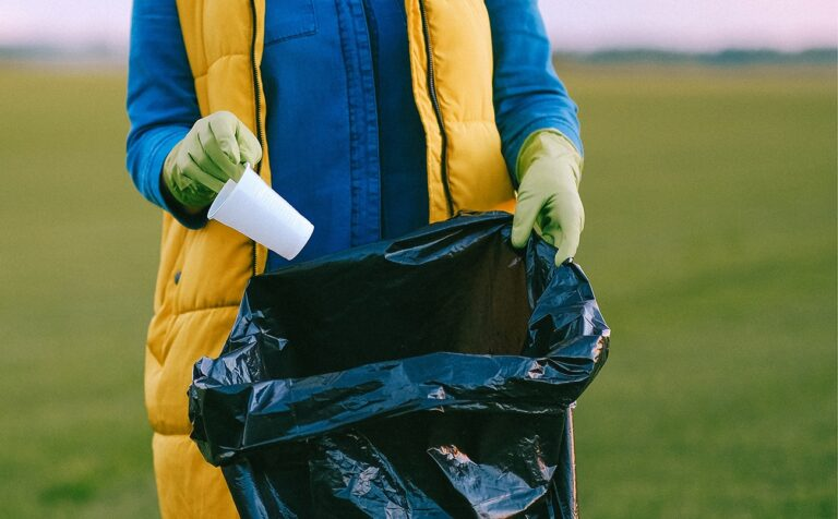 A volunteer putting a plastic piece of trash in a bag during a volunteer cleanup event