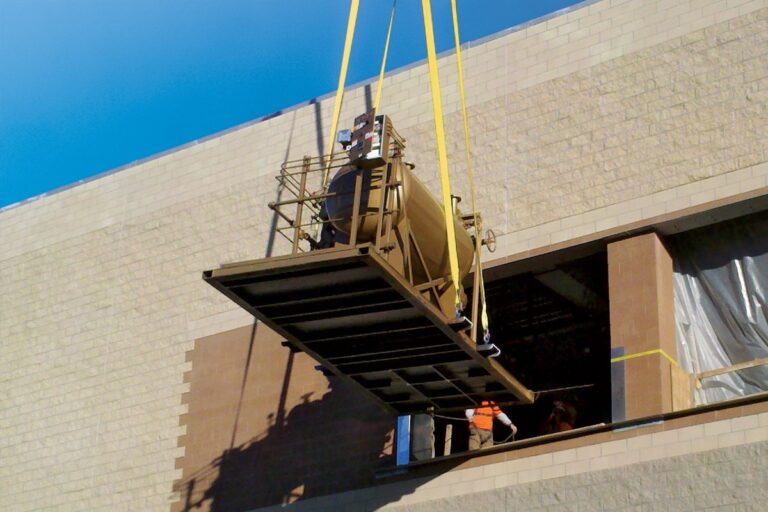 A Fulton Boiler product being delivered by crane into an opening of a building